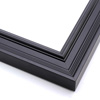 This matte black, ornately ridged crown moulding frame features a steep outer edge that cascades in curved steps into a flat valley.  The inner lip rises again in a gentle, bevelled curve.