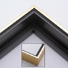 This solid wood canvas floater picture frame features a shiny brushed gold on the outside edge and narrow face.  The long inside step and base are a matte black. 