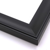 This solid wood frame features a shallow scoop profile subtle ridged edge.  The face is a solid matte black that gently draws the eye toward the artwork.